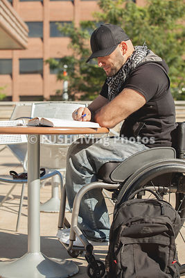 Young man in a wheelchair studying on campus