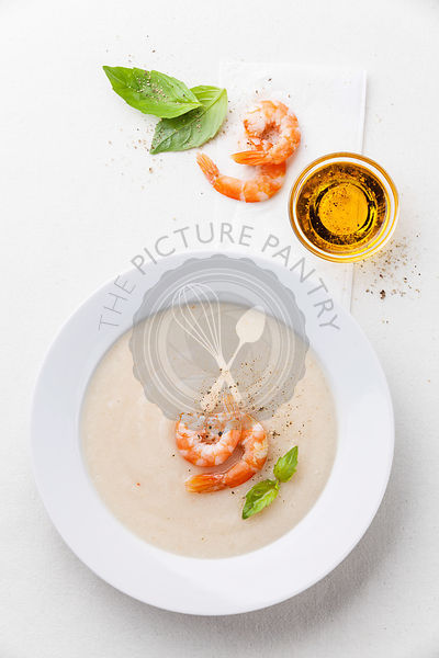 Cauliflower soup with prawns on white background