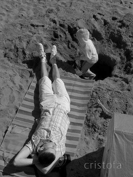 girl plays in a hole while father relaxes on Looe beach