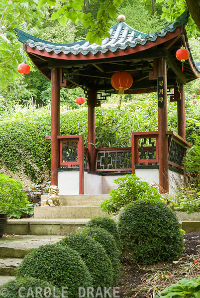 'Harvesting the Moon Pavilion' in the Red Wall garden at top of steps edged with clipped Lonicera nitida and river washed lim...