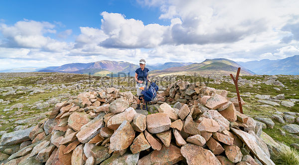 LAKE DISTRICT, CUMBRIA, ENGLAND, UK - SEPTEMBER 02, 2017: A female hiker arrives at the summit shelter of Great Borne with views of Grasmoor, Robinson and Red Pike.