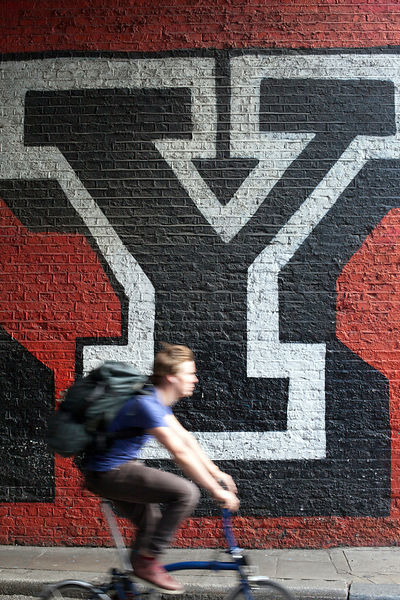UK - London - A man cycles past a large piece of graffiti, Shoreditch