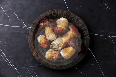 Raw wild Porcini mushrooms on wooden plate on dark marble table background