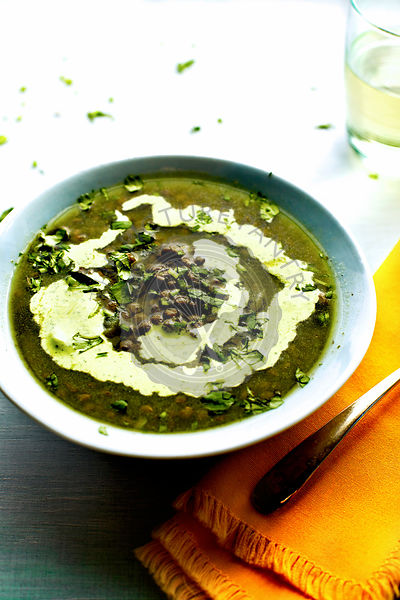 Green Lentil Poblano Soup photographed on a light blue background.