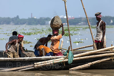 Workers haul baskets of sand from a boat on the Hooghly River in Kolkata, India. It will be used for a construction project.