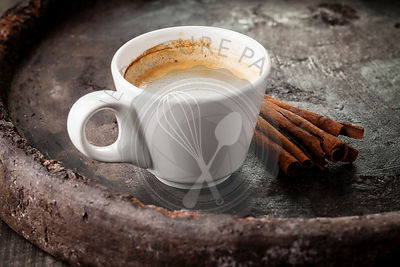 Coffee cup with  cinnamon sticks on dark background