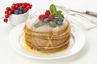 Pile of delicious handmade pancakes topped with raspberries and bilberries
