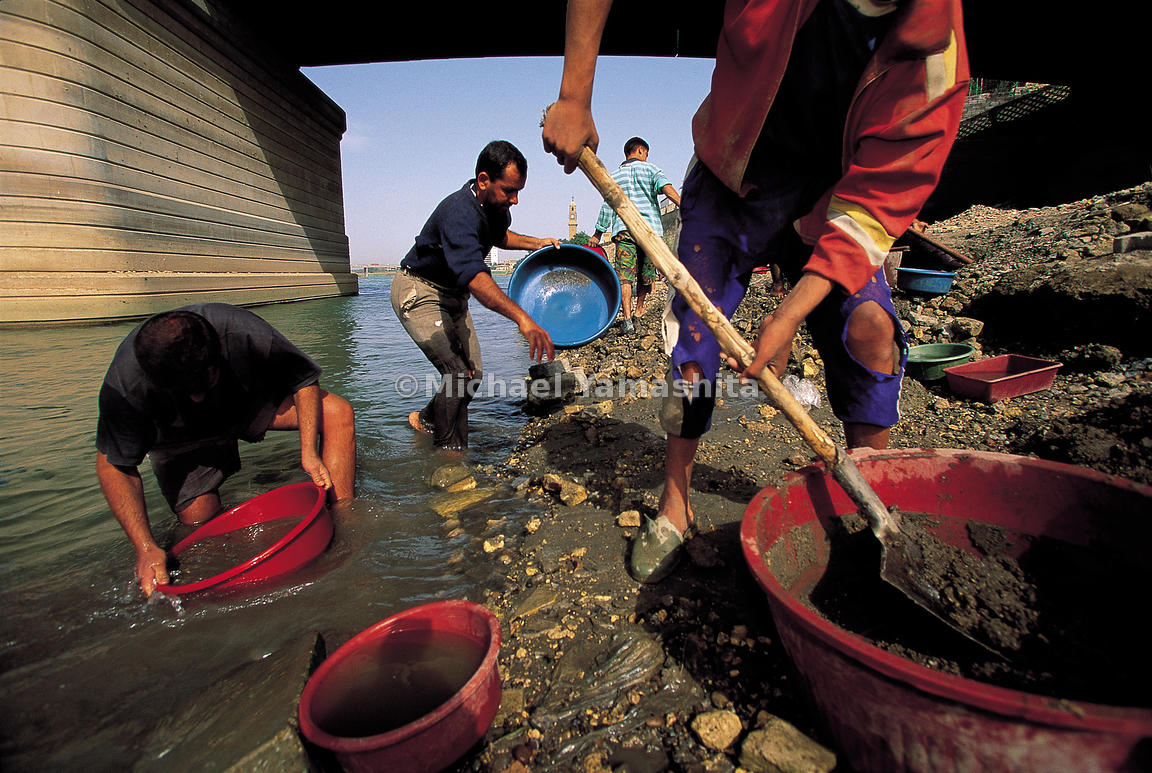 Gold-hunters sieve the river for waste from the nearby goldmiths' souk.