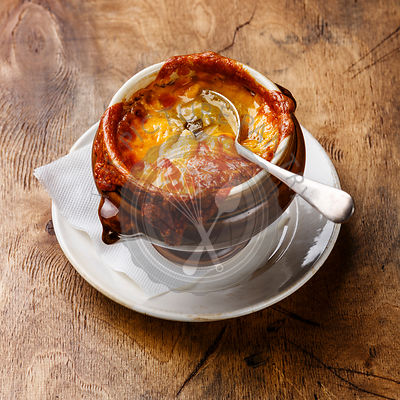 Authentic French Onion soup with dried bread and cheddar cheese in bowl on wooden background