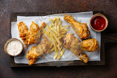 Fried breaded chicken legs fast food with popular sauce on brown background