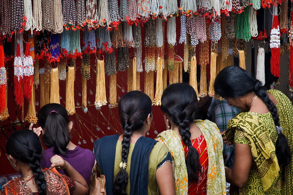 Women with thick braided hair shop for jewelry in Pushkar, Rajasthan, India