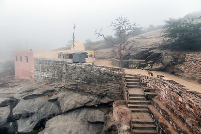 Foggy morning on the awesome country road passing the 7th century Ajaypal Shiva Temple, near Pushkar, Rajasthan, India
