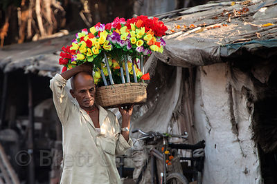 A man carries brightly colored flowers down an otherwise drab street near Kumartoli Ghat, Kolkata, India.