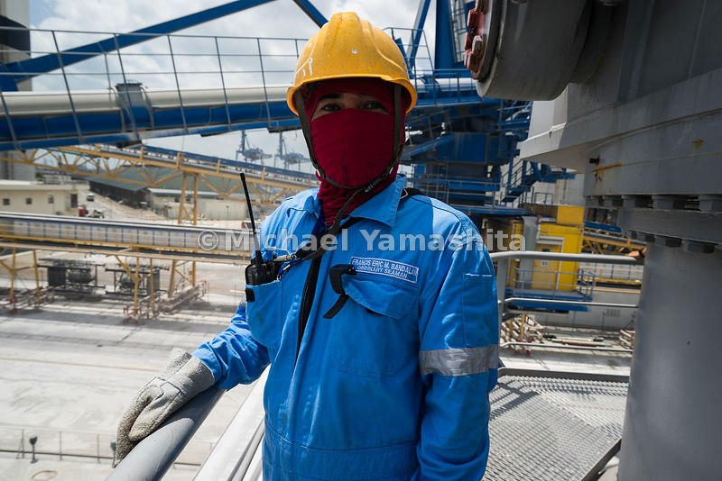 A vessel crewman, donning a helmet and a face mask, stands aboard a cement vessel.