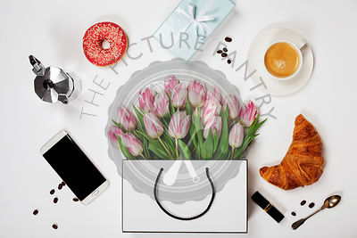 Top view of spring flowers, coffee, mobile phone, croissants, gift and cosmetics. Flat lay image. Holiday, romance of modern ...