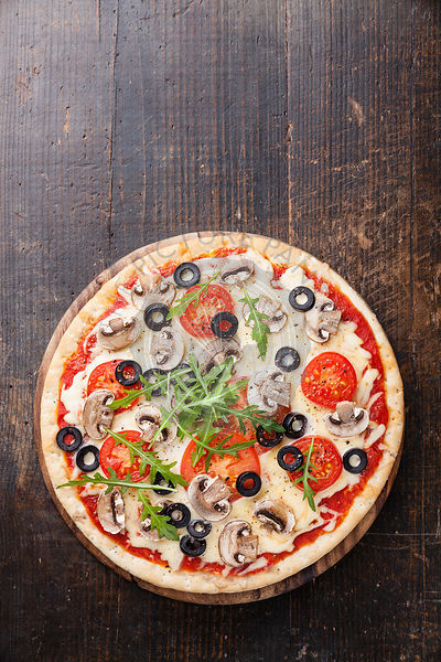 Pizza with mushrooms and ruccola on wooden table