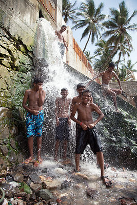 A group of teenage boys washes off in a small waterfall at a popular swimming area, Juhu Beach, Mumbai, India