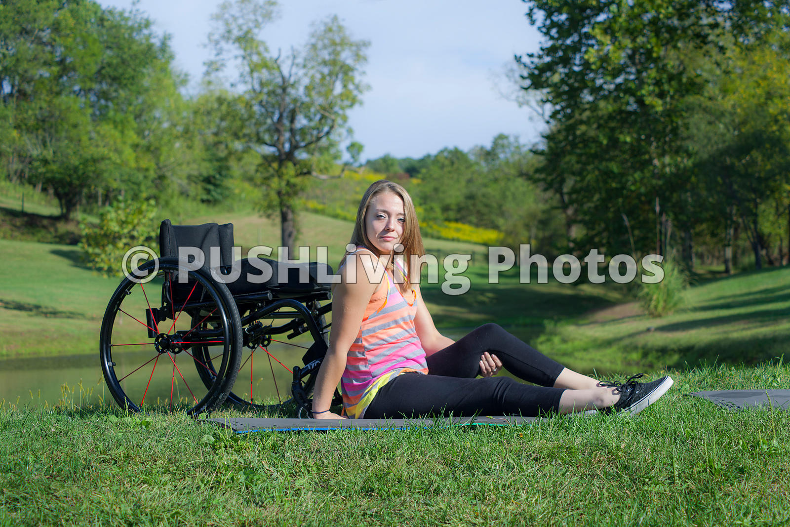 Young woman using a wheelchair exercising in a park