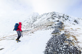 A hiker climbing Sharp Edge on route to the summit of Blencathra (Saddleback) in the Lake District.