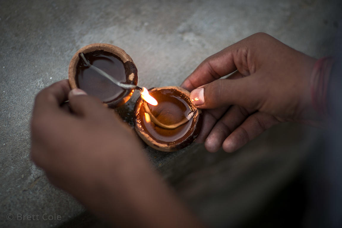 A person lights a diya to set it out on Pushkar Lake as an act of prayer, Pushkar, Rajasthan, India