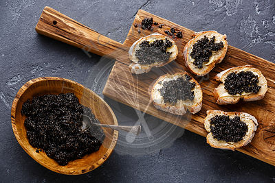 Sturgeon black caviar in wooden bowl and sandwiches on dark stone background copy space