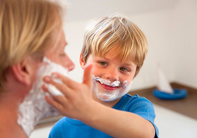 Father and son applying shaving cream