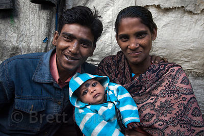 Proud parents and their infant in a slum area in Ward 66, Muchipara, Kolkata, India. Many people in the community make sandals.