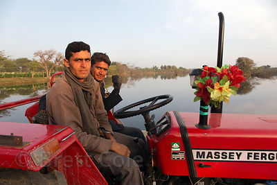 Flower farmers drive their tractor across a bridge over a lake in Maseena village, Rajasthan, India