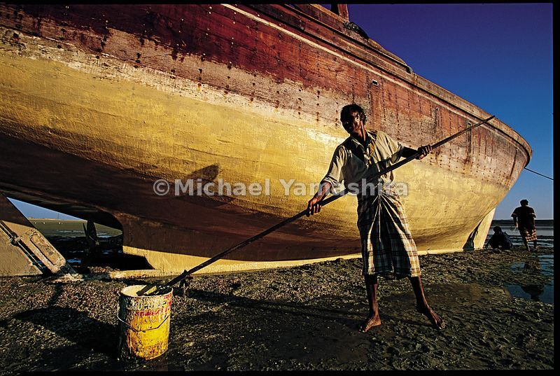 Sailors clean the hull of a dhow in Sur.