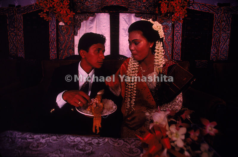 The bride and groom eat from a communal dish. The Batak people, described by Marco Polo as being cannibals are mostly Christi...