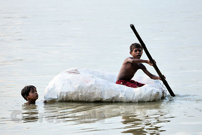 Children collect mud from the Hooghly (Ganges) River on a raft made from plastic bottles. The mud will be used by sculptors t...