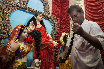 A man attaches hair to an idol of Lakshmi at a pandal in the fish market in Newmarket, Kolkata, India. This is a really unusu...