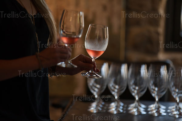 Mid section of a woman with rose wine in a glass