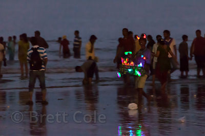 A man in horns sells LED gadgets at night on Juhu Beach, Mumbai, India.