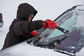 Karen Rentz scrapes ice off the car windshield on Hurricane Ridge while the photographer just stands by, Olympic National Par...