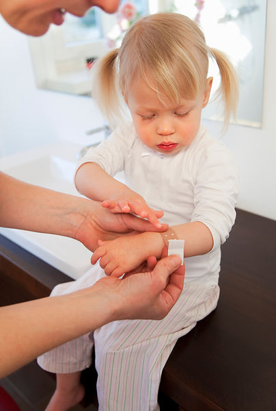Mother putting bandage on toddler girl