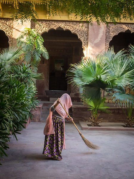 A female worker sweeps the front porch of a historical building