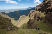 Hikers decending from the escarpment to Twins Cave, Ukhahlamba Drakensberg Park, South Africa
