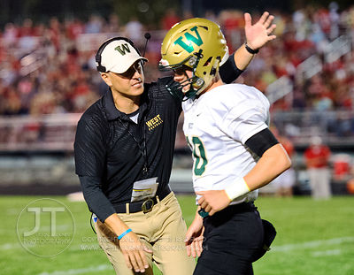 Iowa City West Head Coach Garrett Hartwig congratulates Evan Flitz (10) after a touchdown during the first half of play at Fr...