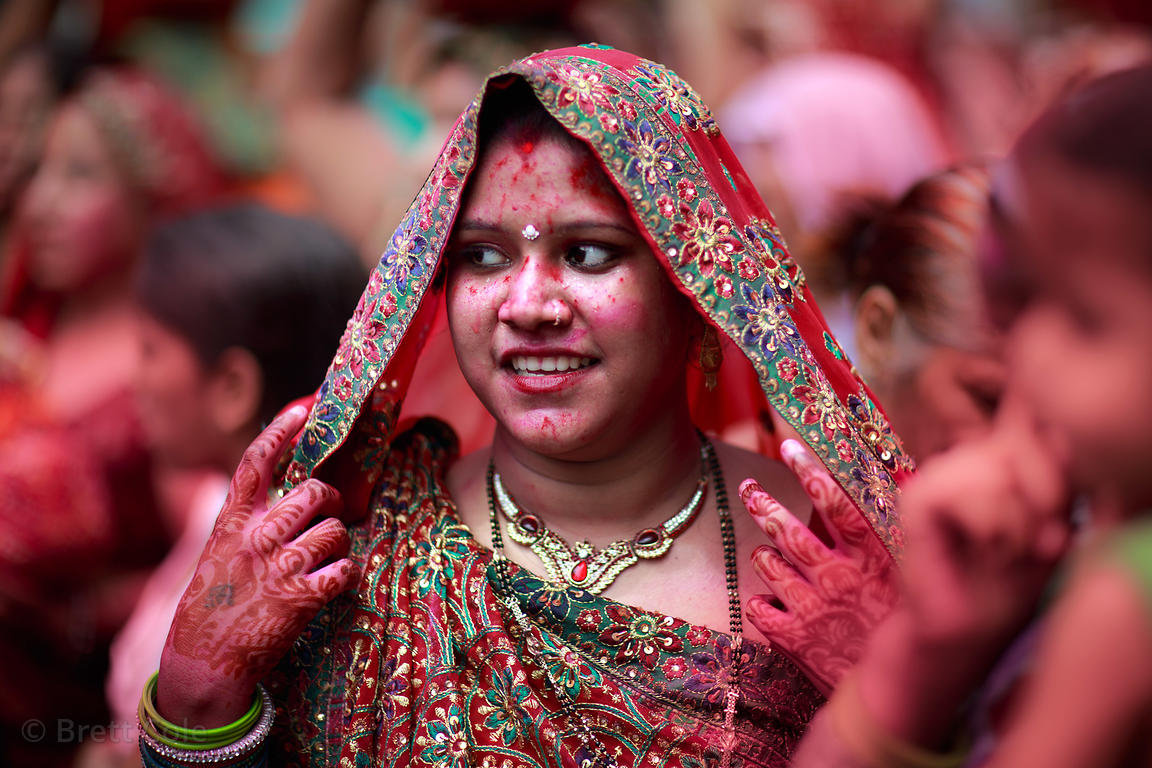 A woman covered in red gulal powder during the Ganesh Chaturthi festival in Delhi, India