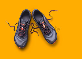 Top view of gray and orange trainers isolated on a yellow background.