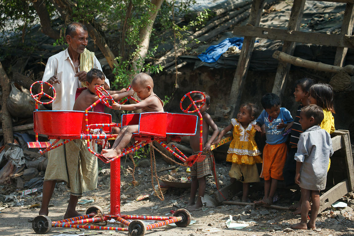 In a poignant scene, an elderly man operates a simple, hand-cranked amusement ride for toddlers near Kumartoli Ghat, Kolkata,...