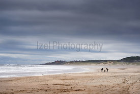 DRURIDGE BAY, ENGLAND, UK - JUNE 03, 2016: A young family out for a walk along the golden sands of Druridge Bay on a windy cl...