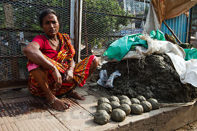 A woman sells balls of mud from the Hooghly River near the Howrah Flower Market, Kolkata, India.