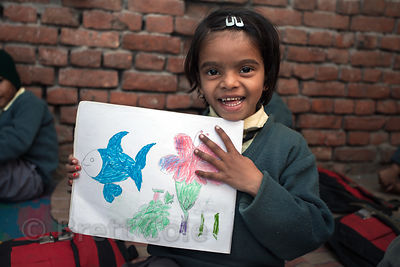 A girl shares her artwork at a school in Varanasi, India operated by Dutch NGO Duniya (duniya.org)