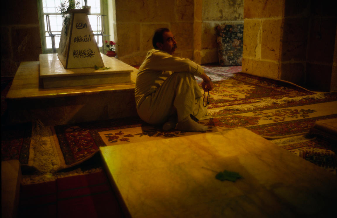 Syria - Aleppo - A man sits amongst tombs