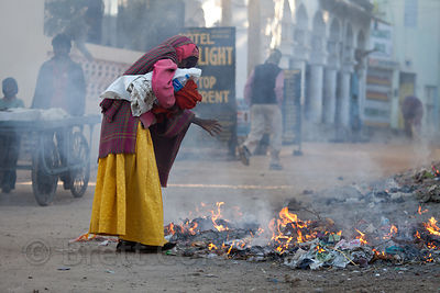 A woman warms her hands in a fire on the streets of Pushkar, Rajasthan, India