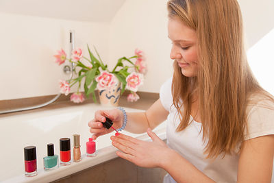 Teenage girl painting her nails