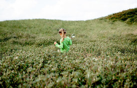 Girl with magnifying glass in Danish dunes 2