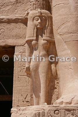 Statue of Nefertari against the leg of her husband, Ramesses II, on the facade of the Sun Temple of Abu Simbel, Egypt